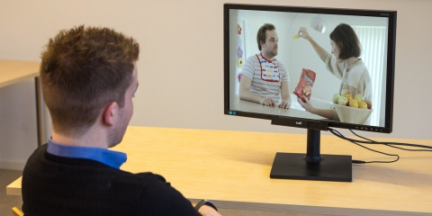 A man watching a TV commercial on a screen with Tobii Pro X2-30 eye tracker mounted on it.
